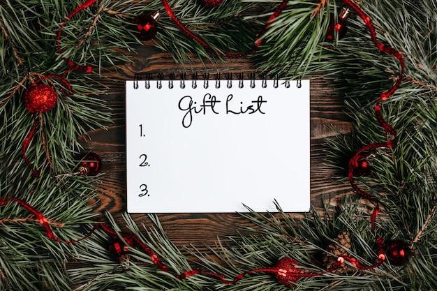 Conceito de feliz natal e feliz ano novo com caixas de presente, brinquedos e caderno com lista de presentes de texto