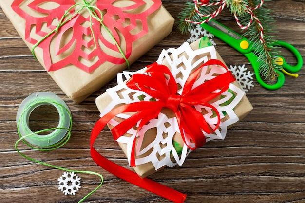 Conceito de feliz natal. embalagem de presentes para o natal em caixas feitas à mão na mesa de madeira.
