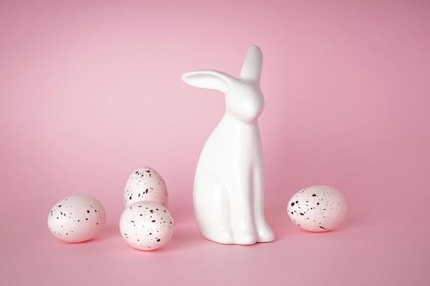Conceito de feliz páscoa. coelhinho da páscoa e ovos de páscoa brancos sobre fundo rosa.