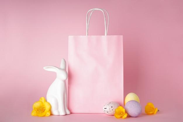 Conceito de feliz páscoa. coelhinho da páscoa e ovos de páscoa coloridos com saco de papel em fundo rosa, lugar para texto