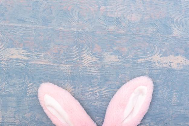 Conceito de feliz páscoa. orelhas de coelho rosa em um espaço de cópia de fundo azul de madeira.