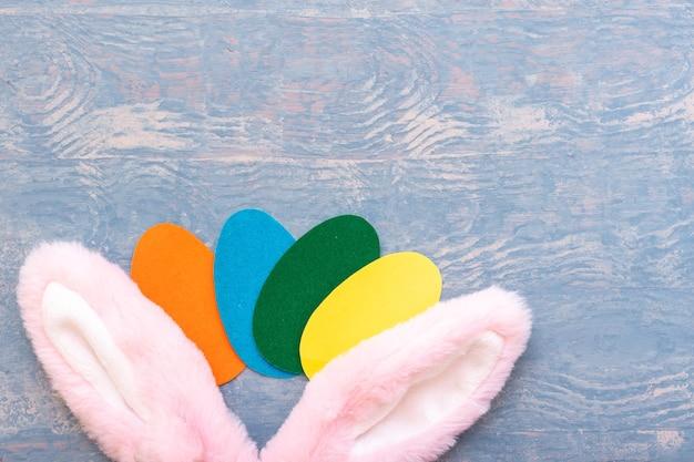 Conceito de feliz páscoa. ovos de páscoa de papel multicolorido e orelhas de coelho rosa em um fundo azul de madeira, cópia espaço, vista superior, postura plana