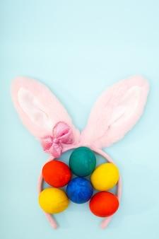 Conceito de feliz páscoa. ovos de páscoa de pintados à mão e orelhas de coelho rosa em uma superfície azul clara, moldura vertical, espaço de cópia. cartão de páscoa minimalista