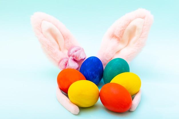 Conceito de feliz páscoa. ovos de páscoa pintados à mão e orelhas de coelho rosa em uma superfície azul, close-up. cartão de páscoa minimalista