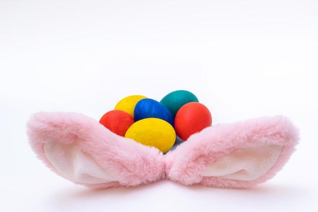 Conceito de feliz páscoa. ovos de páscoa pintados à mão e orelhas de coelho rosa em uma superfície branca. cartão de páscoa minimalista.