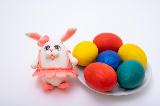 Conceito de feliz páscoa. ovos de páscoa pintados à mão e um coelho de plasticina feito à mão em uma saia rosa na superfície branca, vista superior. faça você mesmo. decoração engraçada.