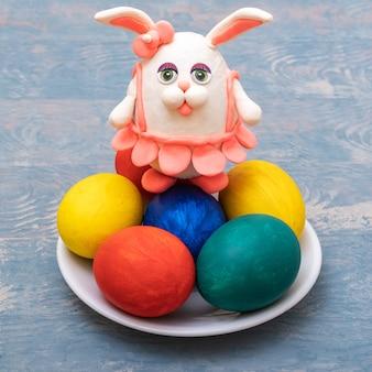 Conceito de feliz páscoa. ovos de páscoa pintados à mão e um coelho de plasticina feito à mão em uma saia rosa sobre uma superfície de madeira azul, close-up, moldura vertical. faça você mesmo. decoração engraçada.