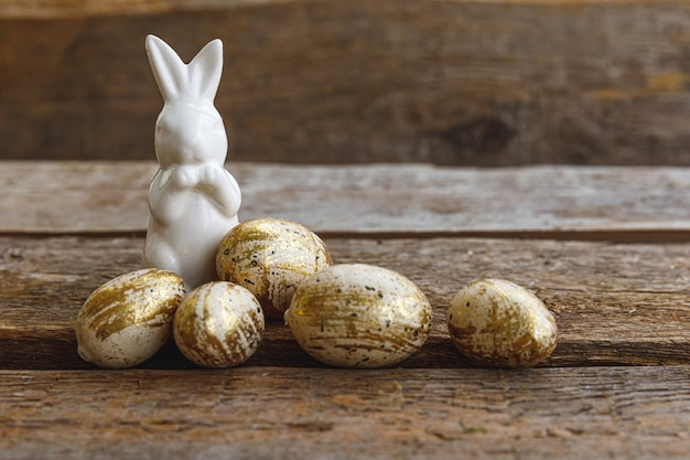 Conceito de feliz páscoa. preparação para férias. ovos de páscoa com decoração dourada e brinquedo de coelho em fundo de madeira