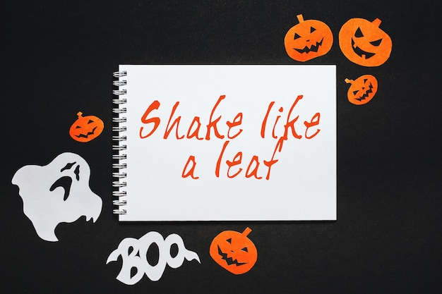 Conceito de feriado de feliz dia das bruxas. bloco de notas com o texto agite como uma folha em fundo preto com morcegos, abóboras e fantasmas