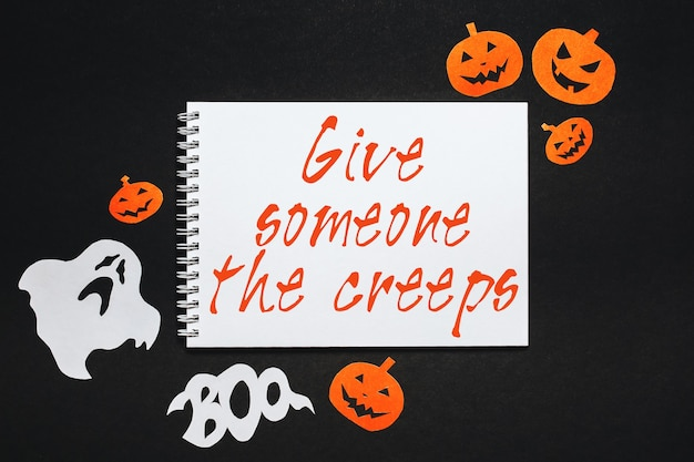 Conceito de feriado de feliz dia das bruxas. bloco de notas com texto deixe alguém arrepiar em fundo preto com morcegos, abóboras e fantasmas