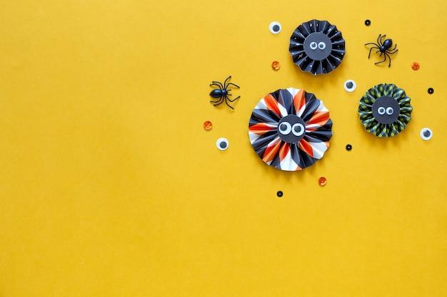 Conceito de feriado de feliz dia das bruxas. decorações de papel diy em fundo amarelo brilhante. maquete de cartão de festa de halloween com espaço de cópia. camada plana, vista superior, banner aéreo.