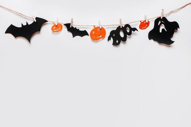 Conceito de feriado de feliz dia das bruxas. morcegos, abóboras e fantasmas na corda com prendedor de roupa em fundo branco isolado