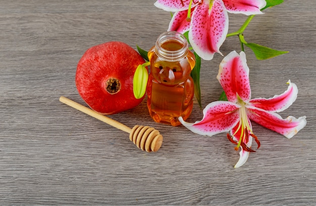 Conceito de feriado judaico de rosh hashaná - romã mel rosa lírios comida judaica, símbolo