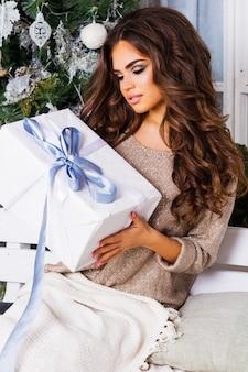 Conceito de feriados, celebração e pessoas - mulher sorridente com roupas aconchegantes e aconchegantes segurando uma caixa de presente branca sobre o fundo da árvore de natal