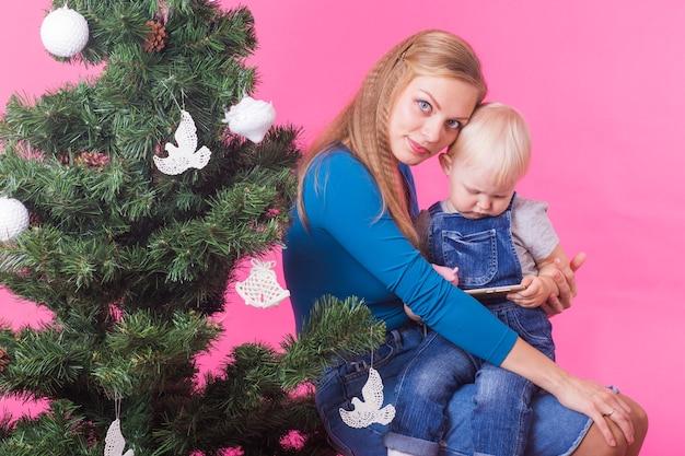 Conceito de feriados e pessoas - mulher e filho perto da árvore de natal no espaço rosa