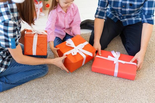 Conceito de feriados e presentes - close de família abrindo presentes na época de natal
