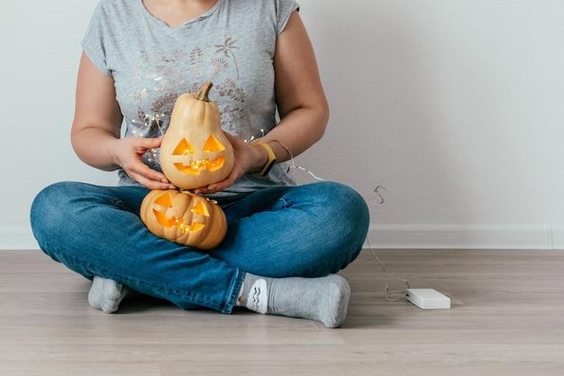 Conceito de feriados, halloween, decoração e pessoas - close-up de mulher com abóboras em casa