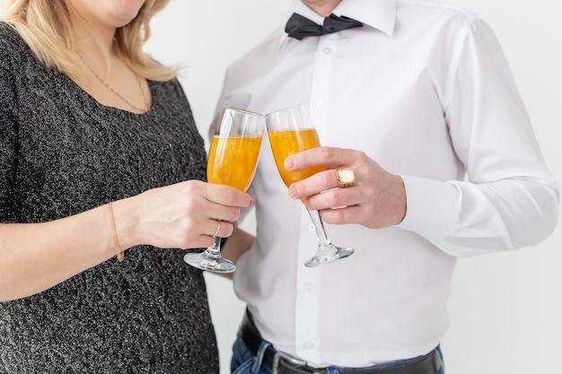Conceito de feriados, natal, dia dos namorados e ano novo - mulher e homem celebram e seguram vinho em um close-up de vidro sobre fundo branco