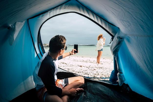 Conceito de férias alternativas de acampamento para viajantes e pessoas com estilo de vida selvagem com um menino tirando fotos para uma mulher na praia curtindo a natureza e o conceito de casa livre