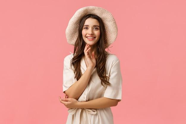 Conceito de férias, beleza e compras. alegre morena glamour concurso feminino vestido, chapéu chique, elegante e bonito sobre rosa, sorrindo tendo conversa casual