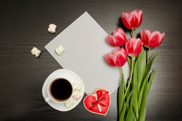 Conceito de férias. buquê de tulipas cor de rosa, uma xícara de café, biscoitos vermelhos em forma de coração com uma nota