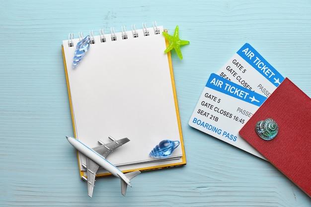 Conceito de férias com passaporte e bilhetes, avião, bloco de notas com espaço de cópia sobre fundo azul de madeira. vista do topo.
