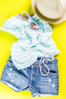 Conceito de férias, conjunto de roupas de criança - shorts para crianças, camiseta, chapéu, óculos de sol, colar de pulseira, tênis,