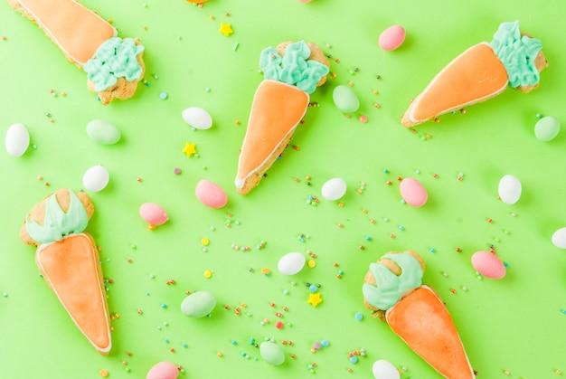 Conceito de férias da páscoa, biscoitos doces em forma de cenoura, coelhinho da páscoa, com granulado doce e balas de ovos, luz de fundo verde cópia espaço vista superior, fundo de cartão
