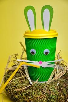 Conceito de férias da páscoa com uma linda xícara de café de papelão verde, com orelhas e uma cara de coelho, decoração artesanal para a páscoa em um fundo amarelo brilhante