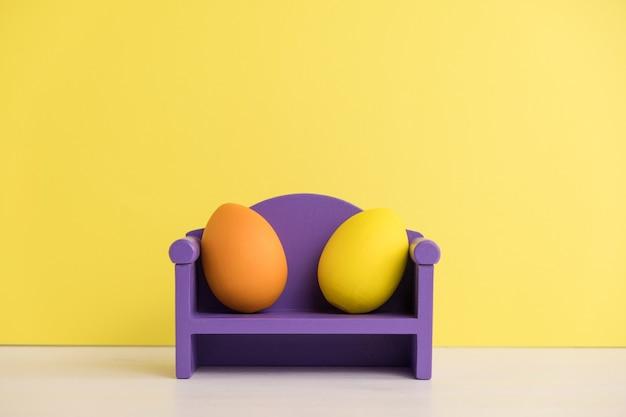 Conceito de férias da páscoa com vida de ovos bonitos. emoções e sentimentos diferentes. ovos de lindo casal sentado no sofá.