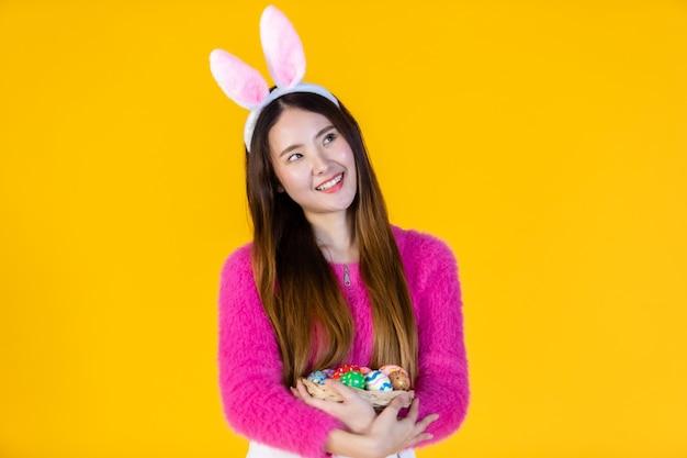 Conceito de férias da páscoa, feliz jovem asiático com orelhas de coelho mão segurando uma cesta com ovos de páscoa coloridos em isolado no fundo amarelo do estúdio do espaço da cópia em branco.