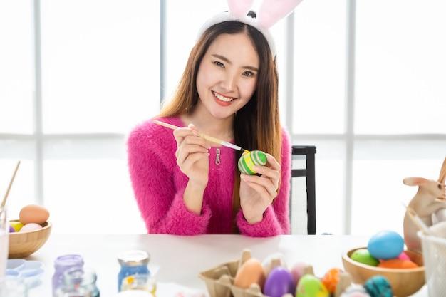 Conceito de férias da páscoa, feliz mulher asiática com orelhas de coelho pintados à mão com ovos para a páscoa com ovos de páscoa coloridos no fundo do quarto branco