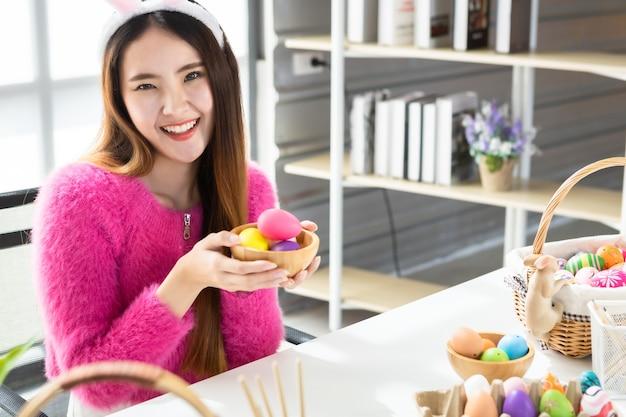 Conceito de férias da páscoa, feliz show asiático jovem segurando uma cesta com ovos de páscoa coloridos no fundo da sala branca