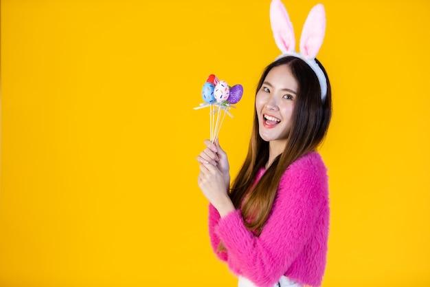 Conceito de férias da páscoa, sorriso feliz mulher jovem asiática usando orelhas de coelho mão segurando espetos de ovos de páscoa coloridos em isolado no fundo amarelo do estúdio do espaço da cópia em branco.