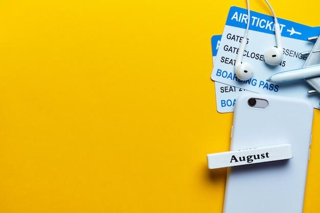 Conceito de férias de agosto com avião em fundo amarelo, com espaço de cópia