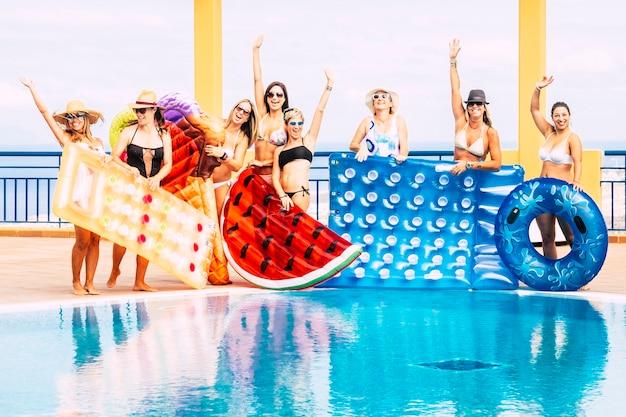 Conceito de férias de férias de verão com grupo de feliz e. mulheres adultas com carinho se divertem juntas na piscina com lilos infláveis coloridos da moda