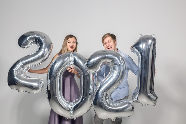 Conceito de férias de festa, pessoas e ano novo - mulher e homem comemorando o ano novo de 2021.