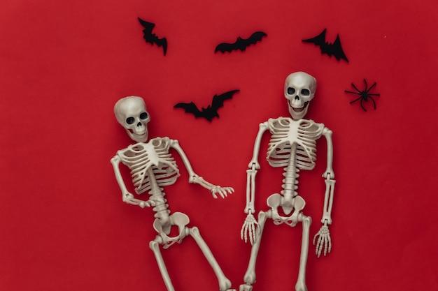 Conceito de férias de halloween. dois esqueletos e morcegos voadores, aranhas em um vermelho