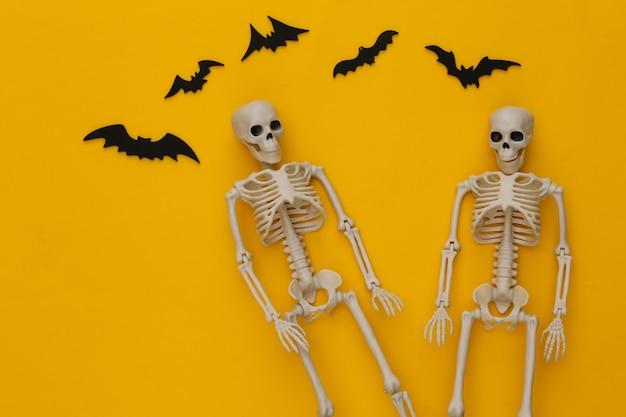 Conceito de férias de halloween. dois esqueletos e morcegos voadores em um amarelo
