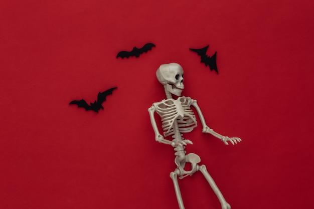 Conceito de férias de halloween. esqueleto e morcegos voadores em um vermelho