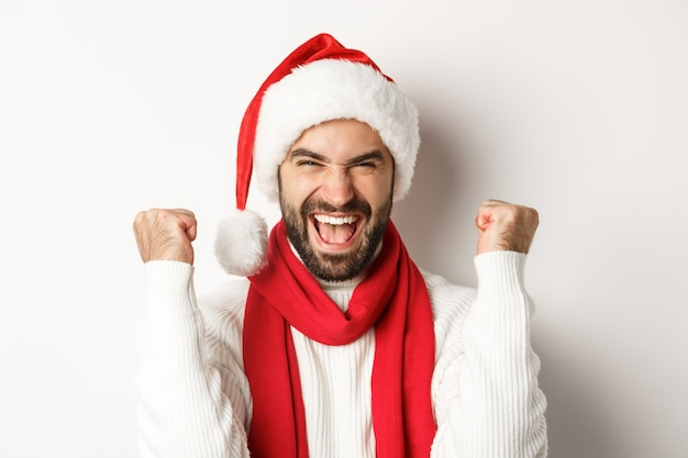 Conceito de férias de inverno e festa de ano novo. close de um homem animado com chapéu de papai noel, regozijando-se, vencendo ou comemorando com chapéu de papai noel, em pé contra um fundo branco
