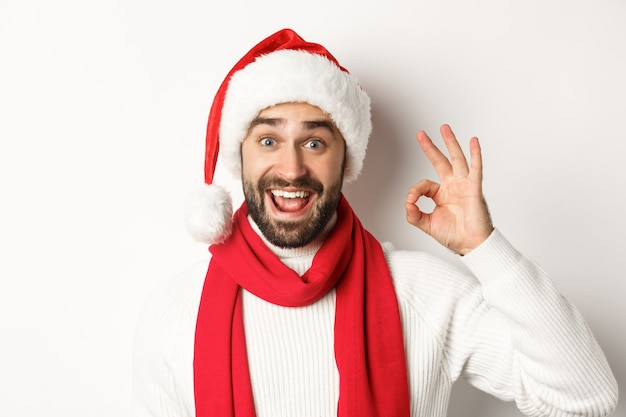 Conceito de férias de inverno e festa de ano novo. close-up de feliz homem atraente com chapéu de papai noel, mostrando sinal de ok, comemorando o natal, fundo branco