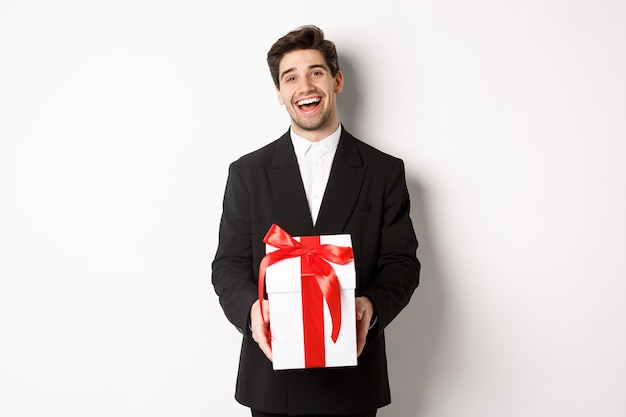 Conceito de férias de natal, celebração e estilo de vida. alegre homem bonito em terno preto, segurando o presente de natal e sorrindo, de pé contra um fundo branco.
