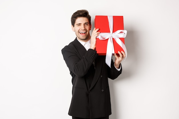 Conceito de férias de natal, celebração e estilo de vida. homem atraente em um terno preto, segurando um presente de ano novo e sorrindo, em pé com um presente sobre fundo branco