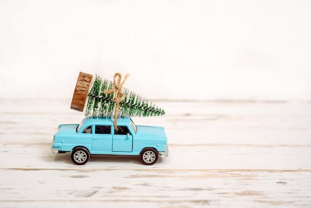 Conceito de férias de natal com pinheiro no carro de brinquedo.