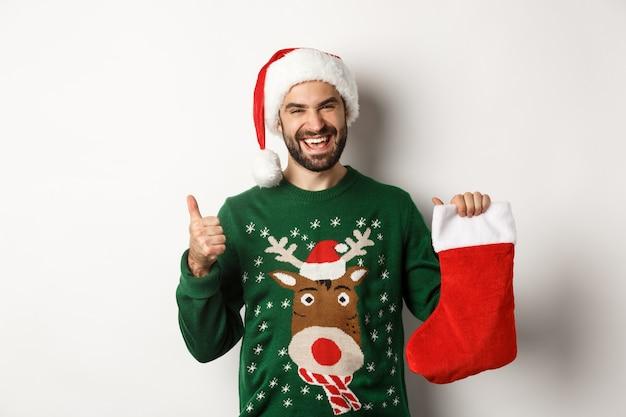 Conceito de férias de natal e inverno. homem feliz e satisfeito com chapéu de papai noel, gostando do presente na meia de natal, mostrando o polegar, em pé sobre um fundo branco