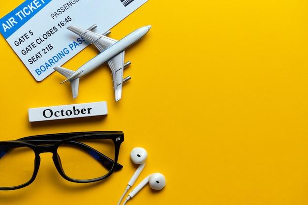 Conceito de férias de outubro ao lado de bilhetes e modelo de avião sobre fundo amarelo, com espaço de cópia.