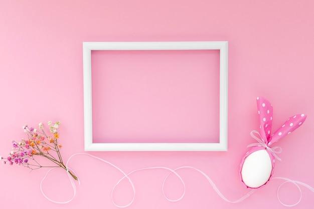 Conceito de férias de páscoa feliz. no ovo de páscoa de fundo rosa com orelhas de coelho e flor de gipsófila e moldura branca com espaço vazio para o texto.