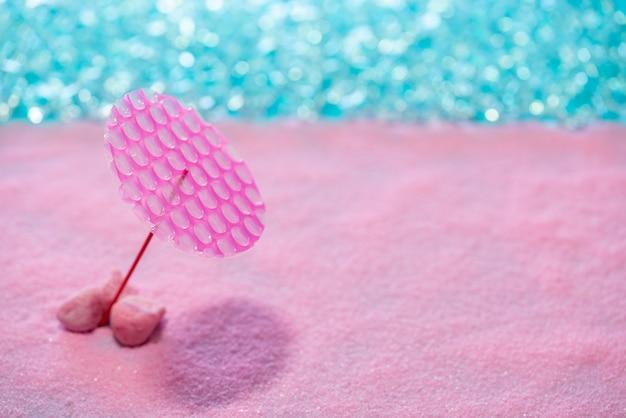 Conceito de férias de praia rosa areia parasol
