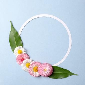 Conceito de férias de primavera. layout criativo feito de flores coloridas com folhas verdes e contorno de cartão de papel em forma de círculo em branco sobre fundo azul pastel. .